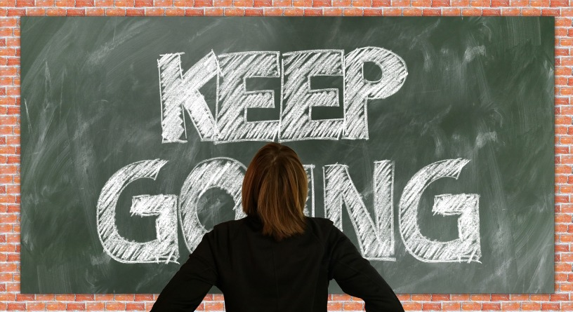 """woman with brown hair and black outfit looking at a green chalkboard on a red brick wall that says, """"keep going"""" in white chalk"""