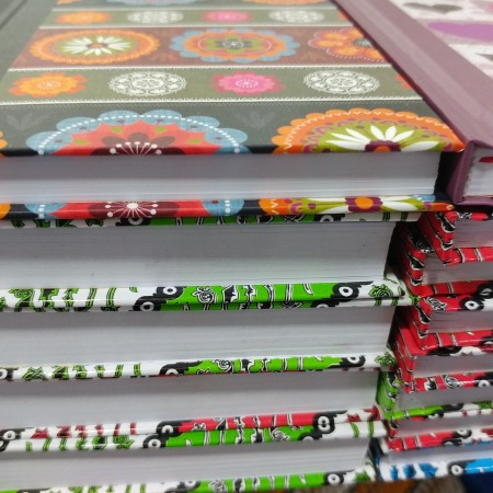 Three stacks of colorful journals or books