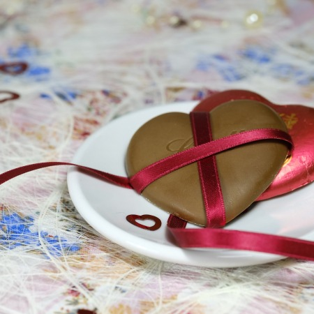 heart chocolate wrapped in red ribbon on a plate on a festive tablecloth