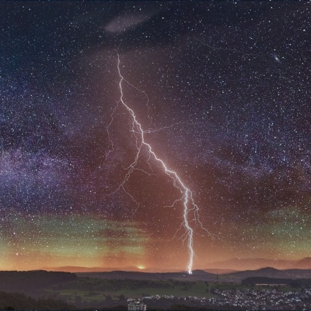nighttime starry sky with huge lightning bolt over city