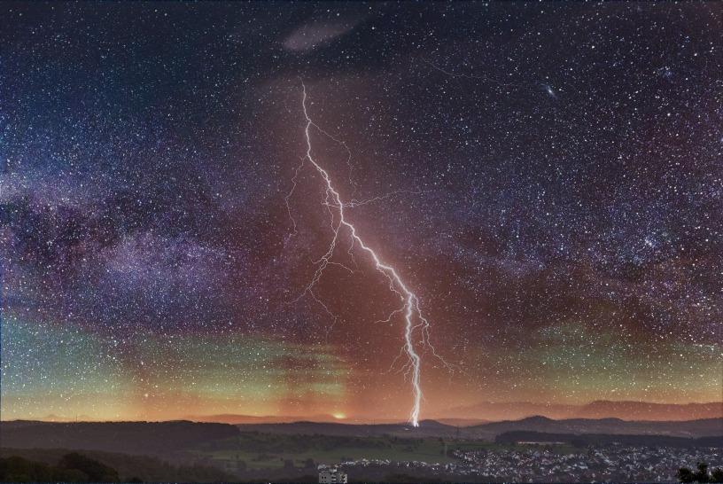 nighttime starry sky with huge lightning bolt over city