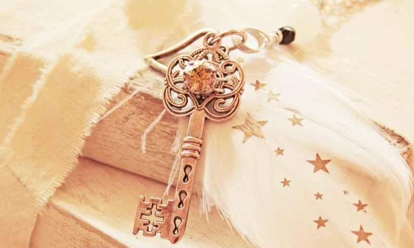 romantic looking golden key on wood and fabric