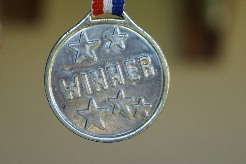 silver medal with red, white, and blue strap that says 'winner'