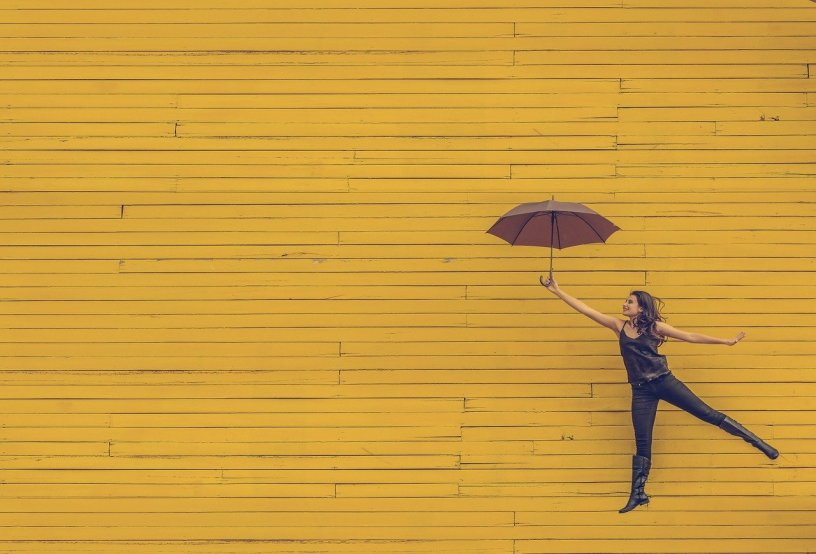 woman holding umbrella jumping against a yellow wall