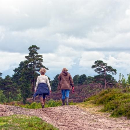 Two women in coats walking a dirt path