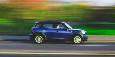 fast moving blue car on road with blurred background