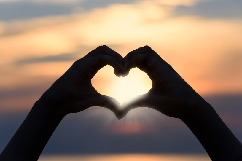 heart made with two hands with sunlight streaming through
