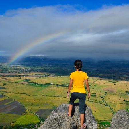 woman on rock looking at rainbow