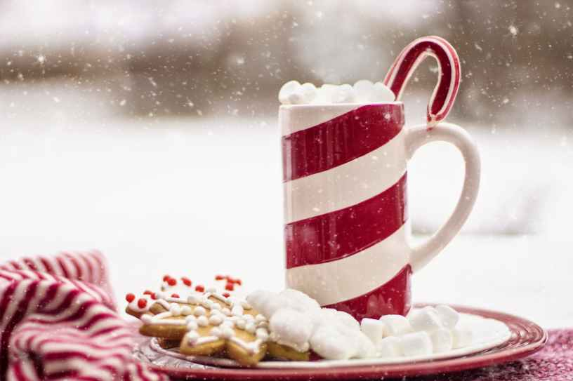 hot chocolate with marshmallows in a candy cane mug with a plate of Christmas decorated cookies sitting outside with snow flying.