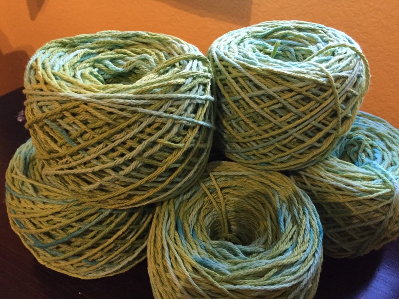 five skeins of blue and green yarn on top of a table
