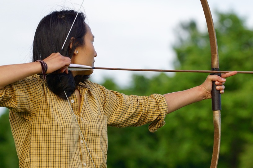 archery; dark haired woman in man's plaid yellow shirt with bow and arrow