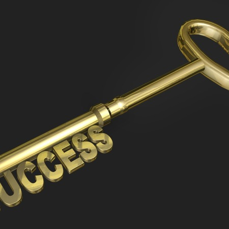 A golden key of success against a black background