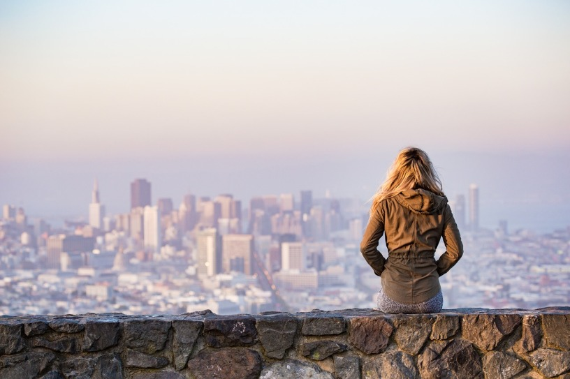 blonde haired woman in jacket sitting on stone bench looking at a city skyline with smog sky