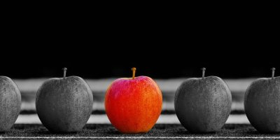 Black and white photo of 5 apples in a row. The center apple is bright red and stands out dramatically from the others.