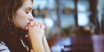 Young girl with long brown hair has eyes closed and hands clasped together in prayer.