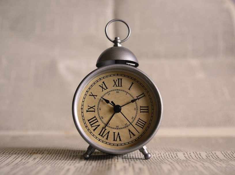 An old fashioned pewter clock says 10:10 with black hands on it's parchment face. The clock sits on top of newspaper with blurred newsprint behind it. The clock has a ring carry handle on top.