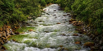 A flowing river bubbles over rocks as it winds along. There are rocks and thick green brush along both sides of the river.