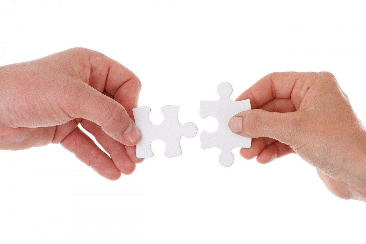 Two hands holding white puzzle pieces together on white background.